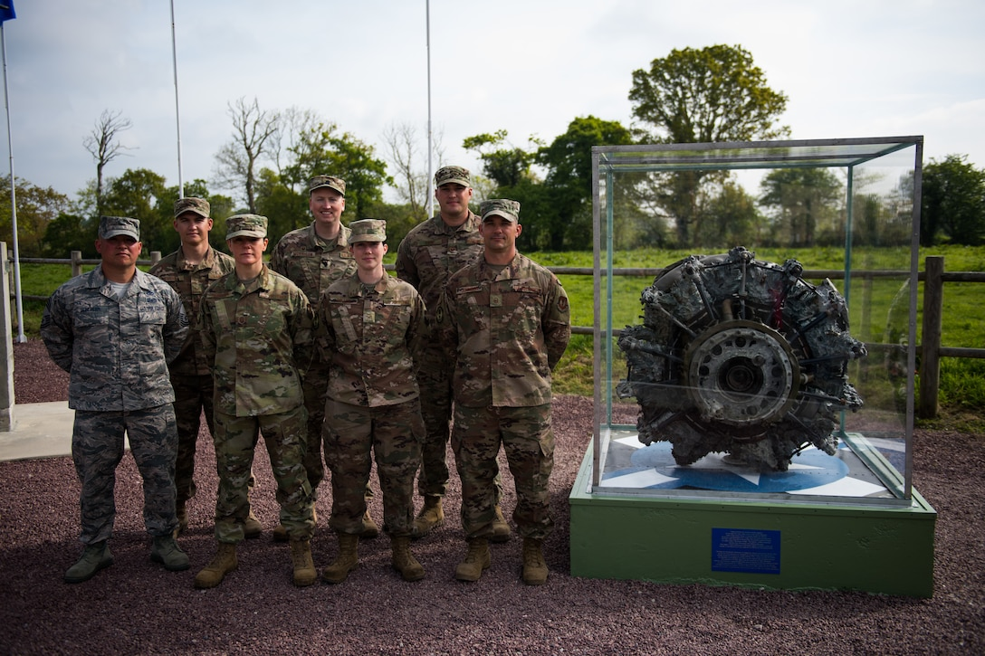 U.S. Air Force Airmen assigned to the 435th Construction Training Squadron, stand at parade rest next to a newly refurbished WWII aircraft engine display in Picauville, France, May 1, 2019. The Airmen worked together to refurbish the display case and the surrounding memorial in preparation for the 75th Anniversary of D-Day. (U.S. Air Force photo by Staff Sgt. Devin Boyer)