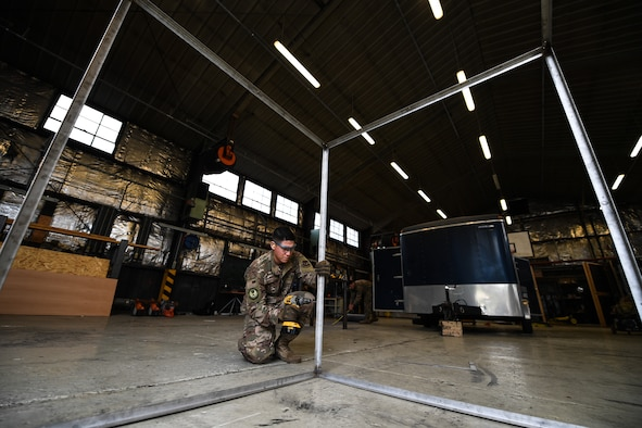 U.S. Air Force Staff Sgt. Matthew Evans, 435th Construction Training Squadron structural contingency instructor, drills holes into a metal frame at the 435th CTS compound near Ramstein Air Base, Germany, April 26, 2019. The frame replaced a display case holding a WWII aircraft engine at a memorial in Picauville, France. (U.S. Air Force photo by Staff Sgt. Devin Boyer)