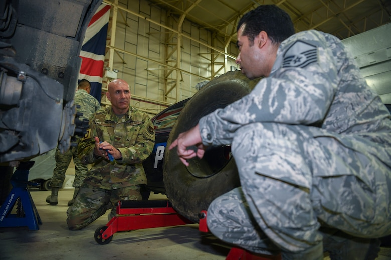 U.S. Air Force Maj. Anthony LaMagna, 100th Logistics Readiness Squadron commander and Master Sgt. Morales Davgene, 100th Logistics Readiness Squadron vehicle fleet manager, check the brakes of an LRS assigned vehicle at RAF Mildenhall, England, May 2, 2019. LaMagna has had his fair number of trials and tribulations. From coming in as an older Airman to losing family members; he overcame personal barriers and struggles throughout his career to fulfill his goal of commissioning. (U.S. Air Force photo by Senior Airman Alexandria Lee)