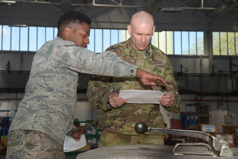 U.S. Air Force Senior Airman Kentral White, 100th Logistics Readiness Squadron traffic management journeyman, and Maj. Anthony LaMagna, 100th Logistics Readiness Squadron commander, look over shipping orders for an outbound package at RAF Mildenhall, England, May 2, 2019. LaMagna participates in 'Walking with Warriors' once a week, where all leadership leave their desk and interact with Airmen, from top leadership on down.   (U.S. Air Force photo by Senior Airman Alexandria Lee)