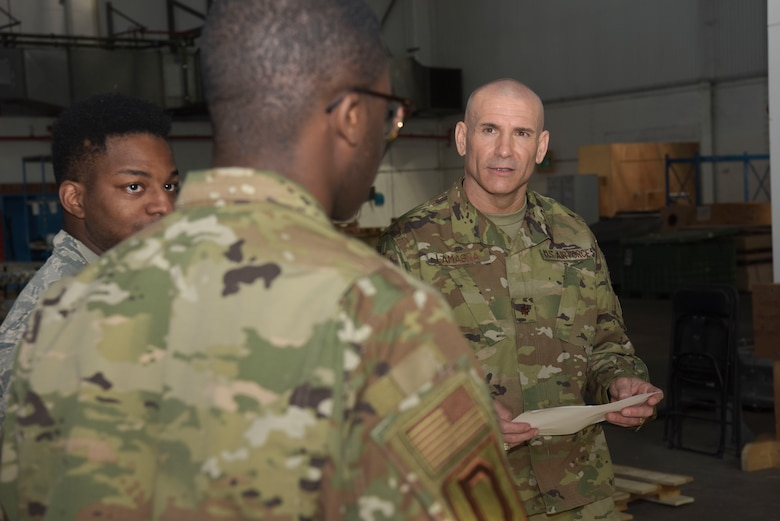 U.S. Air Force Senior Airman Kentral White and Airman 1st Class Jaquavius Johnson, 100th Logistics Readiness Squadron traffic management journeymen, and Maj. Anthony LaMagna, 100th Logistics Readiness Squadron commander, discuss shipping orders for an outbound package at RAF Mildenhall, England, May 2, 2019. LaMagna participates in 'Walking with Warriors' once a week, where all leadership leave their desk and interact with Airmen, from top leadership on down.   (U.S. Air Force photo by Senior Airman Alexandria Lee)