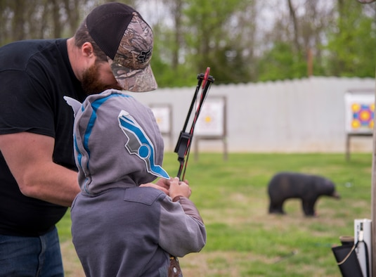 Man helping child with archery bow.