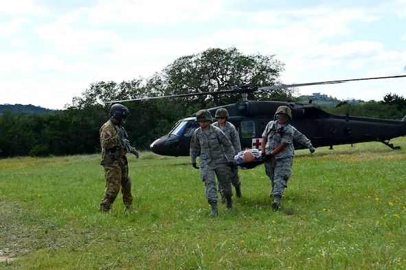 Sgt. 1st Class Dion Cortez, Company C, 2-149 Aviation Texas Army National Guard flight medic, guides Reserve Citizen Airmen medical technicians off-loading a simulated wounded patient by stretcher during Operation Joint Medic May 5, 2019 at Joint Base San Antonio-Camp Bullis, Texas.