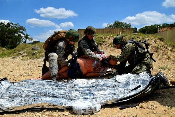 Reserve Citizen Airmen medical technicians and a Navy Reserve corpsman care for a simulated wounded patient during Operation Joint Medic May 5, 2019 at Joint Base San Antonio-Camp Bullis, Texas.