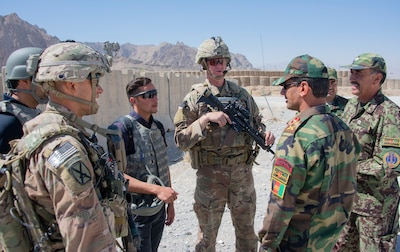 Sgt. 1st Class Jeremiah Velez, left, and Capt. David Zak, center, both advisors with the 1st Security Force Assistance Brigade's 3rd Squadron, speak with their Afghan National Army counterparts during a routine fly-to-advise mission at Forward Operating Base Altimur, Afghanistan, Sept. 19, 2018. (Photo Credit: Sean Kimmons)