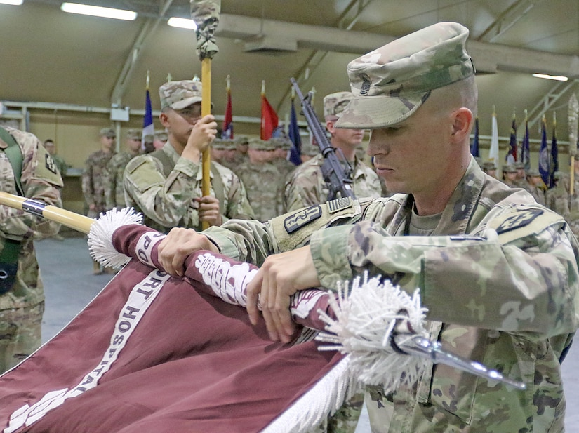 Command Sgt. Maj. Kristopher Orlowski, 452d Combat Support Hospital, prepares to case the unit's colors during the transfer of authority ceremony for United States Military Hospital - Kuwait at Camp Arifjan, Kuwait, May 6, 2019.