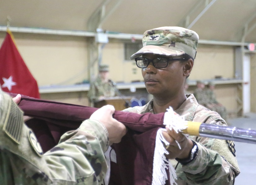 Col. Betty Demus, 349th Combat Support Hospital commander, uncases the unit's colors during a transfer of authority ceremony for United States Military Hospital-Kuwait at Camp Arifjan, Kuwait, May 6, 2019.