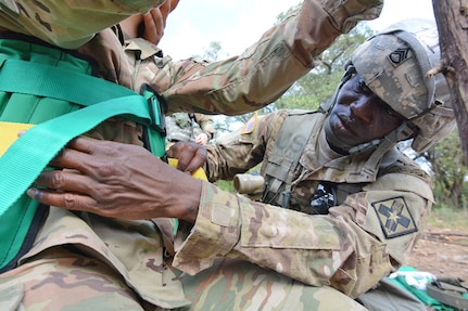 Staff Sgt. Olayiwola Kugblenu, a 68P Nuclear Medicine Specialist with the 264th Medical Battalion, straps a simulated causality into a Kendrick Extraction Device at the Expert Field Medical Badge test event at Joint Base San Antonio-Camp Bullis.