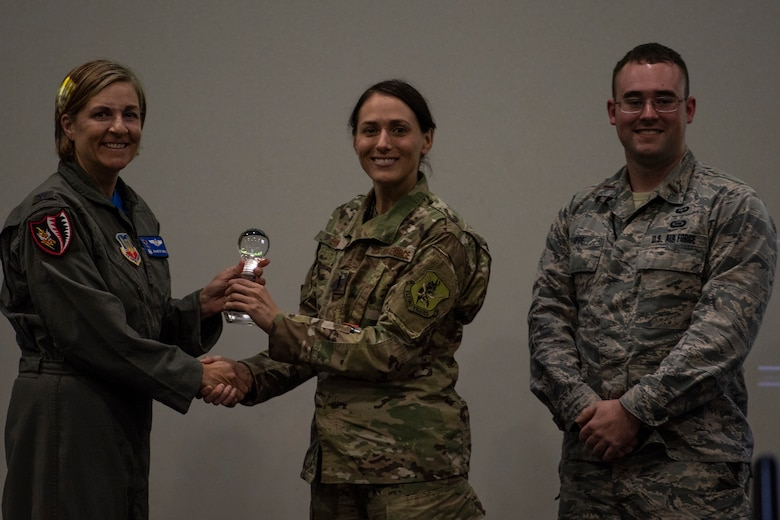 """Col. Jennifer Short (left), 23d Wing commander, presents team 'NightWatch' the first place trophy for their idea May, 3, 2019, at Moody Air Force Base, Ga. Team 'NightWatch"""" pitched an idea that would help make a difference in tracking and assessing global threats. This idea received funding and support from Moody. (U.S. Air Force photo by Airman 1st Class Joseph P. Leveille)"""