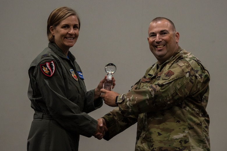 Col. Jennifer Short (left), 23d Wing commander, presents Tech. Sgt. Kevin Grabowsky from team 'Motorola Wave' with the second place trophy May, 3, 2019, at Moody Air Force Base, Ga.  The 'Motorola Wave' team pitched an idea that would increase land mobile radio capabilities on Moody. This idea received funding and support from Moody. (U.S. Air Force photo by Airman 1st Class Joseph P. Leveille