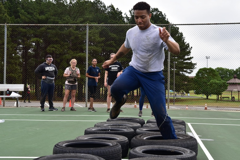 An Airman runs through a tire obstacle during a CLEAR challenge.