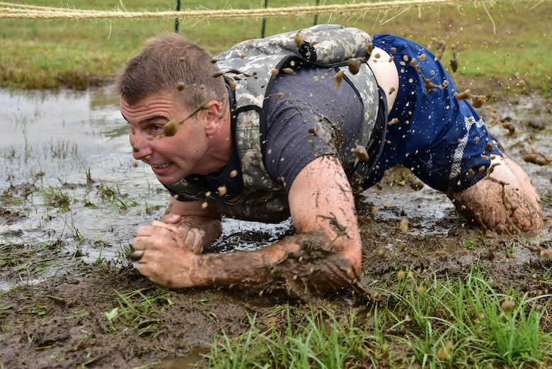 An Airman low crawls through the mud during the SAPR CLEAR challenge.