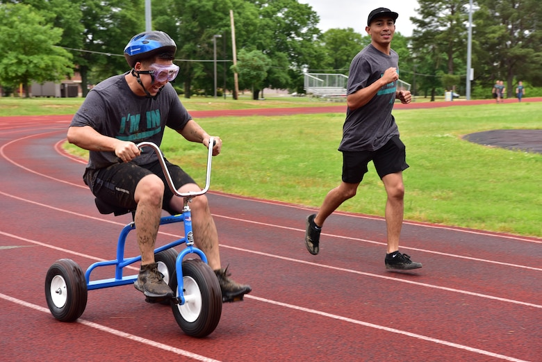 An Airman rides a tricycle during SAPR CLEAR challenge.
