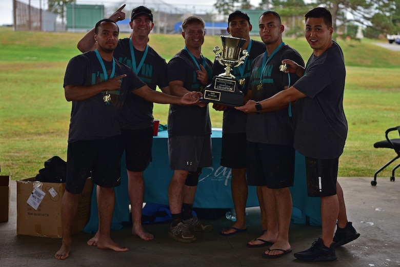 Airmen hold up a trophy after winning the CLEAR challenge.