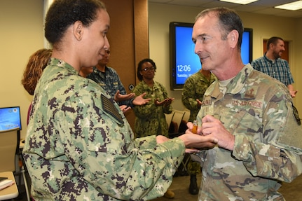 "Air Force Lt. Col. Robert Johnson, 628th Air Base Wing chaplain, right, blesses the hands of Naval Health Clinic Charleston nurse, Lt. j.g. Lakesa Williams, during a ""Blessing of the Hands"" ceremony May 7, 2019, at NHCC located on Joint Base Charleston - Weapons Station, S.C., in celebration of National Nurses Week May 6-12."