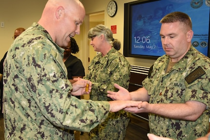 """Navy Lt. Timothy Delaughter, chaplain, left, blesses the hands of Naval Health Clinic Charleston nurse and interim director of NHCC Healthcare Business, Lt. Cdr. Mike Cornell, during a """"Blessing of the Hands"""" ceremony May 7, 2019, at NHCC located on Joint Base Charleston - Weapons Station, S.C., in celebration of National Nurses Week May 6-12"""