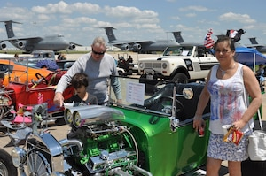 Tech. Sgt. Mark Henson, 433rd Maintenance Group, shows his wife and grandson one of the many classic cars on display at the 433rd Airlift Wing family day May 5, 2019 at Joint Base San Antonio-Lackland, Texas.