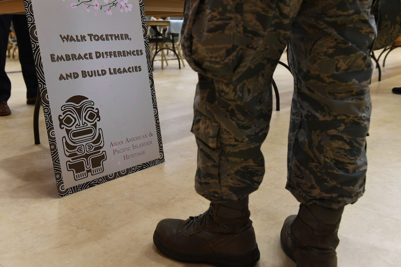 A person's feet stand in front of a sign on the ground and in front of a table.