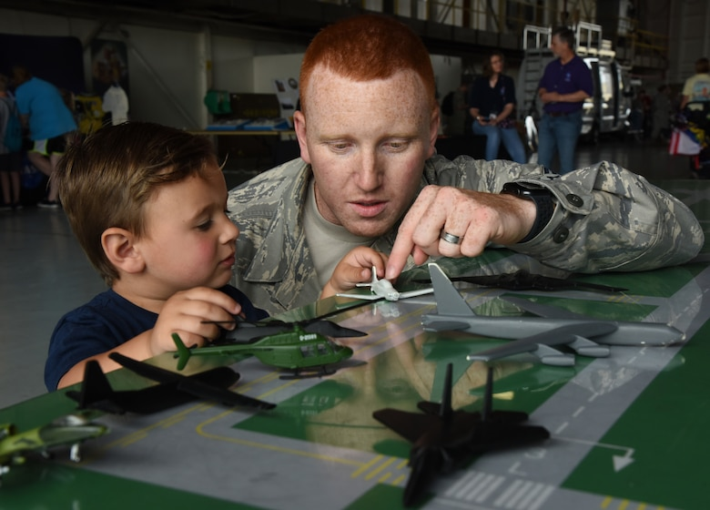 A training instructor uses toy airplanes to provide an air traffic control demonstration