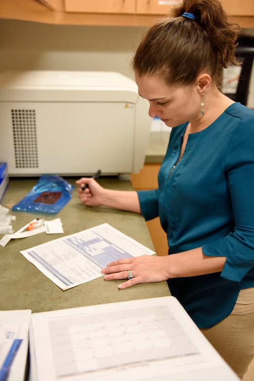 U.S. Air Force Captain Stephanie Smiddy, the infection and immunization officer-in-charge at the 180th Fighter Wing, Ohio Air National Guard, fills out paperwork for blood samples being submitted for testing, Feb. 26, 2019, at the University of Toledo Medical Center where she works as the head research nurse in the precision oncology program at the Eleanor N. Dana Center. Smiddy is responsible for patient care, administrative and regulatory duties. (U.S. Air National Guard photo by Staff Sgt. Shane Hughes)