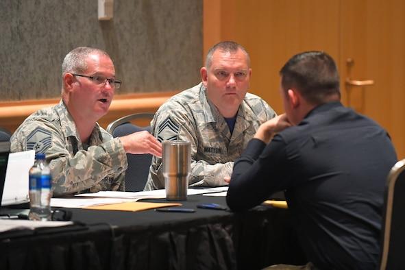 Senior Master Sgt. Craig Fowler (left) and Chief Master Sgt. Matthew Matysik speak with a potential recruit during a hiring fair