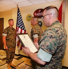 Brig. Gen. Joseph F. Shrader, commanding general, Marine Corps Logistics Command, stands at attention in front of Lt. Gen. Charles G. Chiarotti, deputy commandant, Installations and Logistics, Headquarters Marine Corps, while MARCORLGOCOM's Sgt. Maj. Michael Rowan reads Shrader's promotion warrant. 