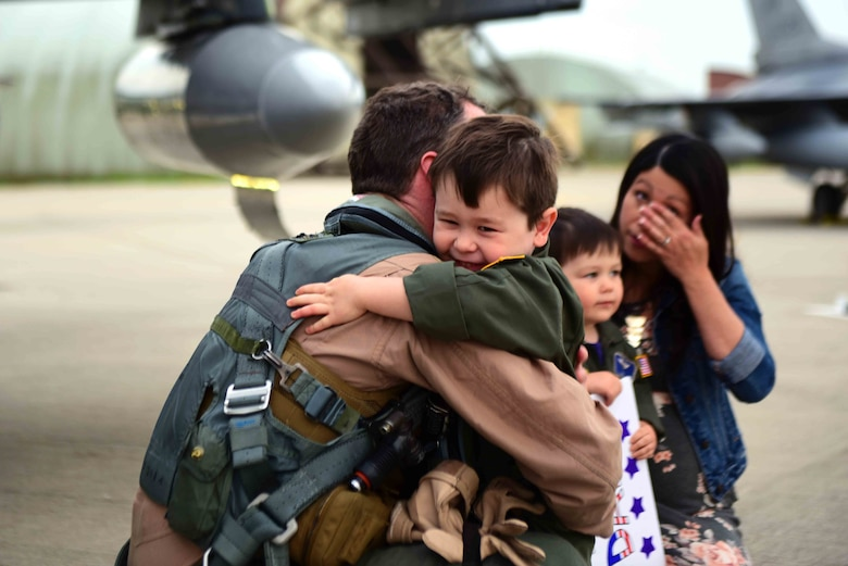 A 510th Fighter Squadron Airman returns home from a deployment and hugs his son at Aviano Air Base, Italy, April 30, 2019. Airmen returning home from deployment must start the re-integration process. (U.S. Air Force photo by Senior Airman Kevin Sommer Giron)