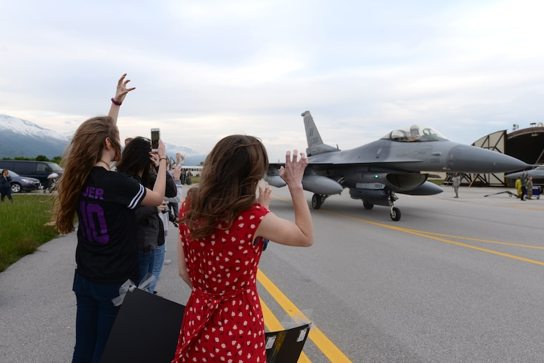 Families greet Airmen from the 510th Fighter Squadron arriving at Aviano Air Base, Italy, April 30, 2019.  510th FS Airmen were deployed to Bagram Air Field, Afghanistan, where they flew 7,500 combat hours and executed more than 1,000 sorties to deter adversaries and execute the National Defense Strategy. (U.S. Air Force photo by Senior Airman Kevin Sommer Giron)