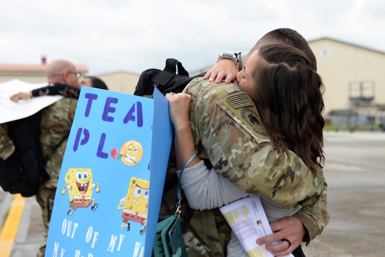 A 31st Fighter Wing Airman returns home from a deployment and embraces his spouse at Aviano Air Base, Italy, May 9, 2019. The Airman and Family Readiness Center provided various support programs for families of deployed members, including monthly family dinners. (U.S. Air Force photo by Senior Airman Kevin Sommer Giron)