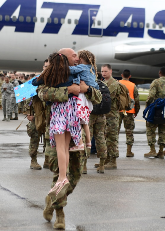 A 31st Fighter Wing Airman returns home from a deployment and hugs his daughters at Aviano Air Base, Italy, May 9, 2019. Down range, 31st FW Airmen flew 7,500 combat hours and executed more than 1,000 sorties to deter adversaries and execute the National Defense Strategy. (U.S. Air Force photo by Senior Airman Kevin Sommer Giron)