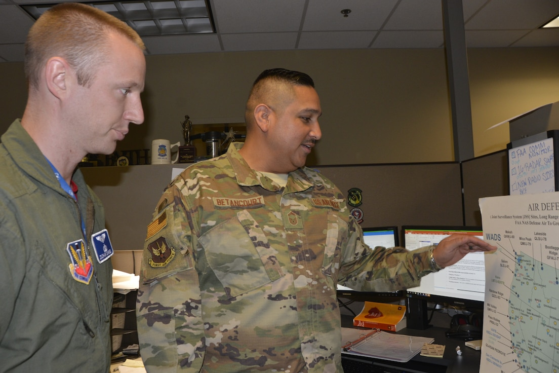 Capt. Zachary Darnell and Senior Master Sgt. Ricardo Betancourt, Air, Space and Information Operations Directorate, discuss air-defense operations. (Photo by Mary McHale)