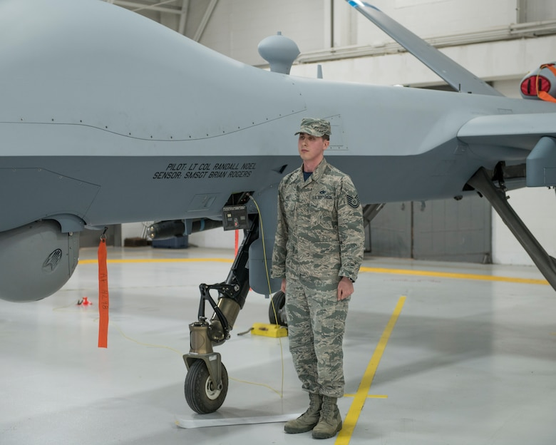 Staff Sgt. Mele ceremoniously unveils the name of the 491st Attack Squadron commander and their Dedicated Crew Chief on the side of an MQ-9 Reaper, during a squadron activation and assumption of command ceremony, May 8, 2019, on Hancock Field Air National Guard Base, N.Y. Lt. Col. Randall Noel, the 491st ATKS commander, formerly led the 6th and 16th Attack Squadrons on Holloman Air Force Base, N.M., as the Director of Operations. (U.S. Air Force photo by Airman 1st Class Kindra Stewart)