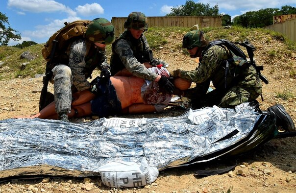 Air Force Reserve medical technicians and a Navy Reserve corpsman care for a simulated wounded patient during Operation Joint Medic May 5 at Joint Base San Antonio-Camp Bullis. The medics carried the patient by stretcher from a simulated firefight to a safer area to administer care until the patient could be evacuated by a Humvee and then onto a UH-60 Blackhawk from the Texas Army National Guard.