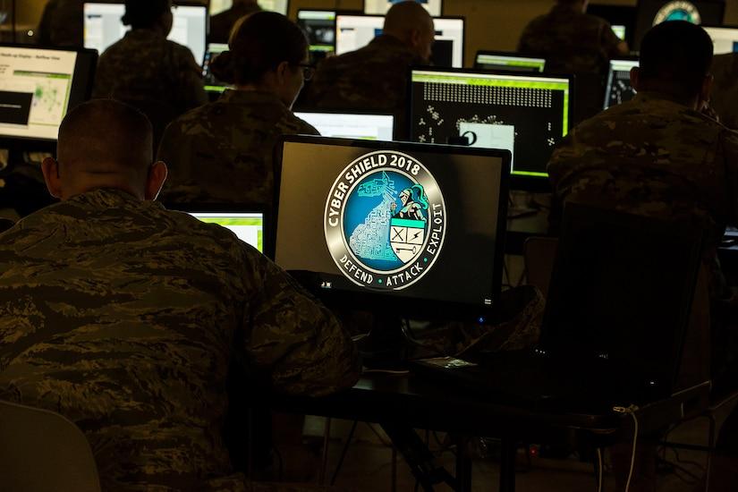 Service members look at laptop screens.