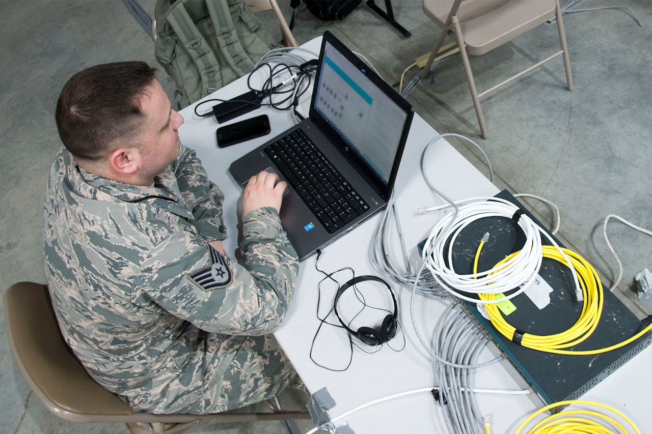 An overhead view of an airman working at a laptop.