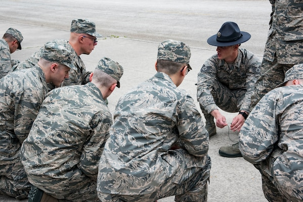 Tech. Sgt. Michael Shurling, 323rd Training Squadron military training instructor, shows his trainees how to properly tie boot laces May 1, 2019, at Joint Base San Antonio-Lackland, Texas. The 323rd TRS Provides world-class military leadership and training necessary to transform recruits into highly motivated Airmen possessing the foundational warrior attitudes, knowledge, skills and abilities to sustain the world's greatest Air Force. (U.S. Air Force photo by Senior Airman Stormy Archer)