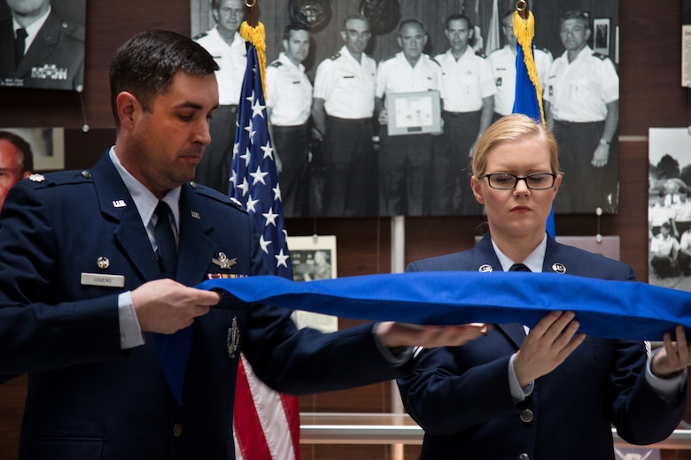Lt. Col. Bill Havens, 42nd Combat Training Squadron commander, and Master Sgt. Kathryn Tichawa case the furled Reserve National Security Space Institute guidon during a redesignation ceremony May 5, 2019.