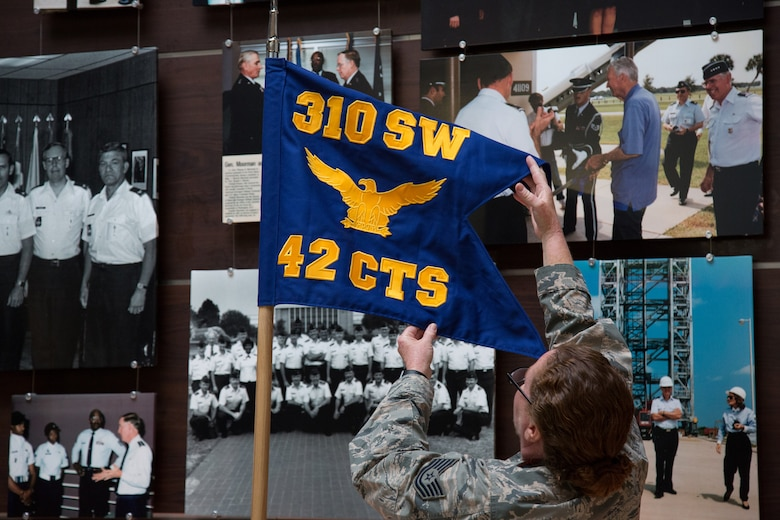 Tech. Sgt. Sarah Corrice, 42nd Combat Training Squadron, displays the new guidon flag for the 42 CTS during a redesignation ceremony May 5, 2019.