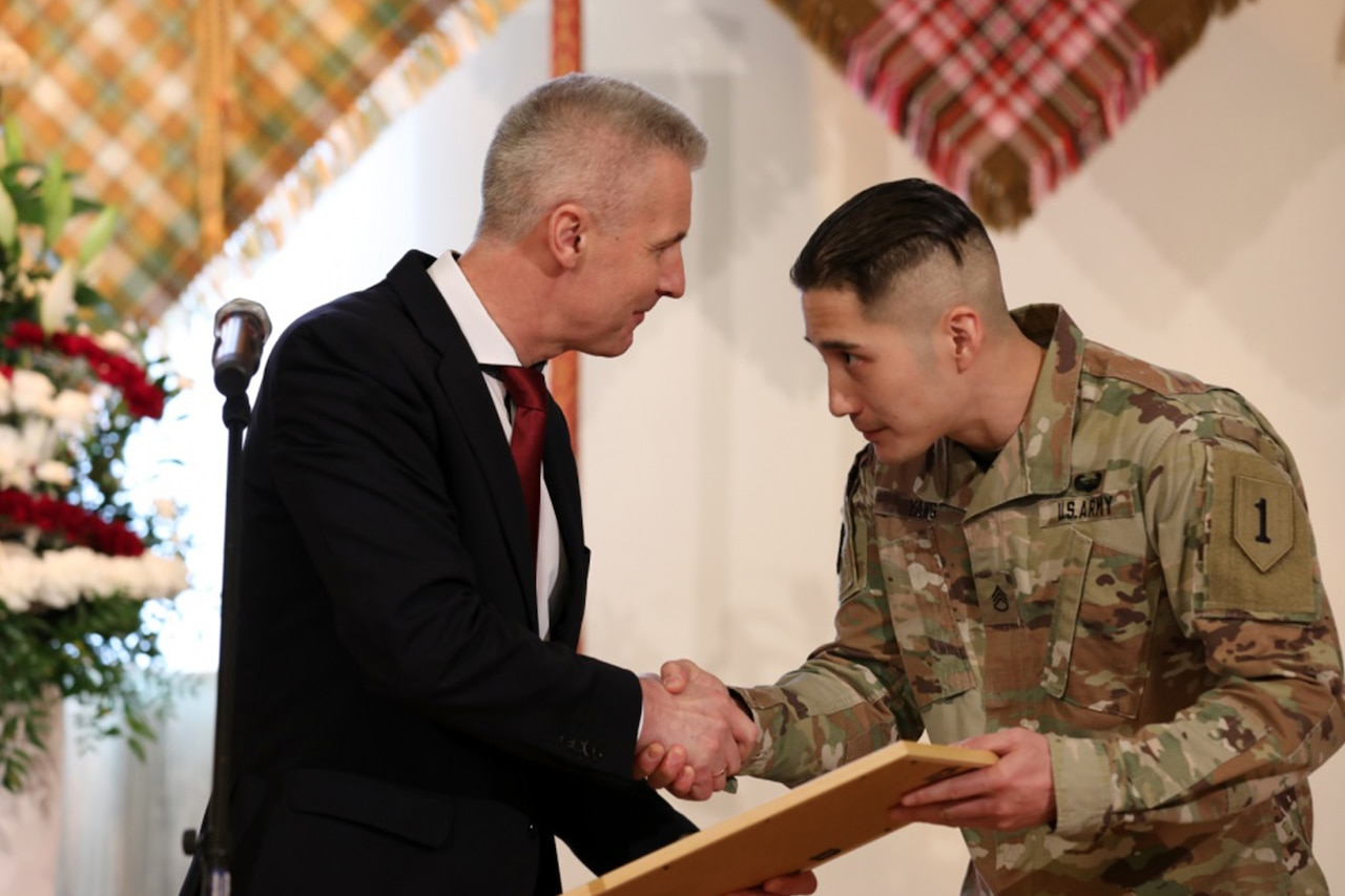 A man in a suit presents award to soldier in uniform.