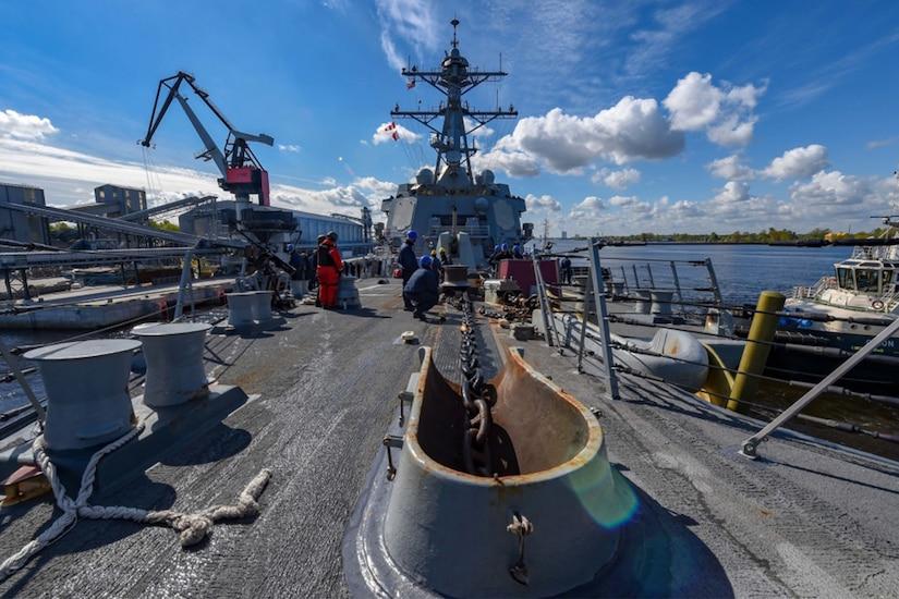 Sailors work on a ship's deck.