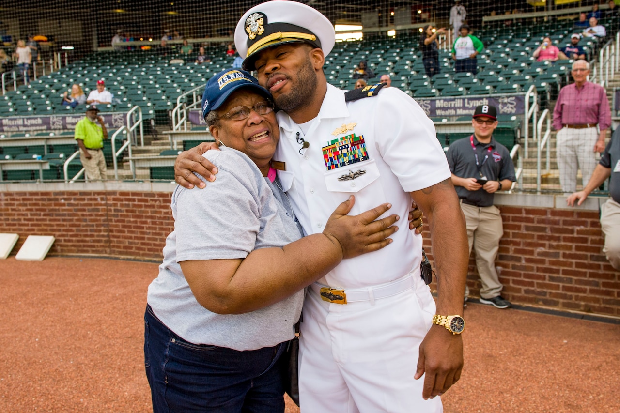 Sailor surprises mother at a baseball game.