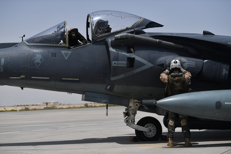 Two U.S. Marines conduct pre-flight checks on an AV-8B Harrier II during Desert Flag 19-2 in Southwest Asia, April 28, 2019. Desert Flag is designed to exercise combined Air Forces in military operations to enhance competence and strengthen military-to-military relationships and regional security.