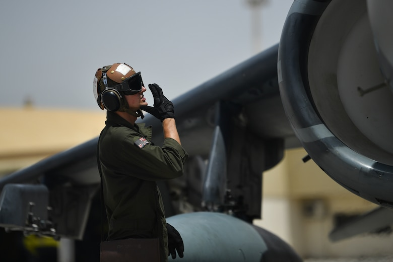 A U.S. Marine communicates with the pilot of an AV-8B Harrier II before taking off during Desert Flag 19-2 in Southwest Asia, April 28, 2019. Desert Flag is designed to exercise combined Air Forces in military operations to enhance competence and strengthen military-to-military relationships and regional security.