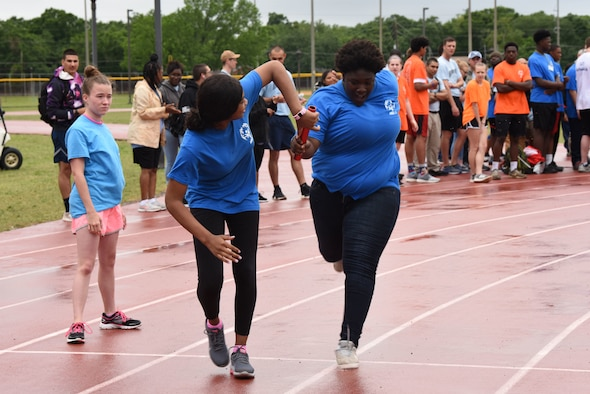 Serenity Stennis, Area 11 athlete, gets the baton to complete the 4x400 relay during the Special Olympics Mississippi 2019 Summer Games at Keelser Air Force Base, Mississippi, May 10, 2019. This is the first year that unified relays have been done during the Special Olympics Mississippi Summer Games. It is a product of a program that allows special olympics athletes and able-bodied athletes from local Mississippi high schools come together to compete in a 4x400 relay. (U.S. Air Force photo by Senior Airman Jenay Randolph)
