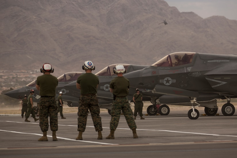 Marines stand with their arms folded as pilots prepare their aircraft for takeoff.
