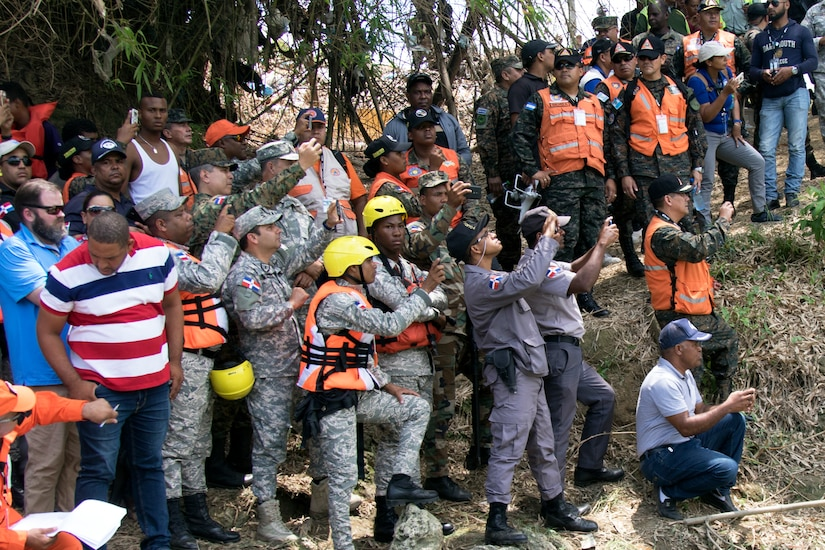 Representatives from Dominican Republic governmental and non-governmental agencies, alongside partner-nation military representatives, watch simulated water rescues take place in a river near Bajo Yuna, Dominican Republic May 9, 2019 as part of Fuerzas Humanitarias Humanitarias 2019.