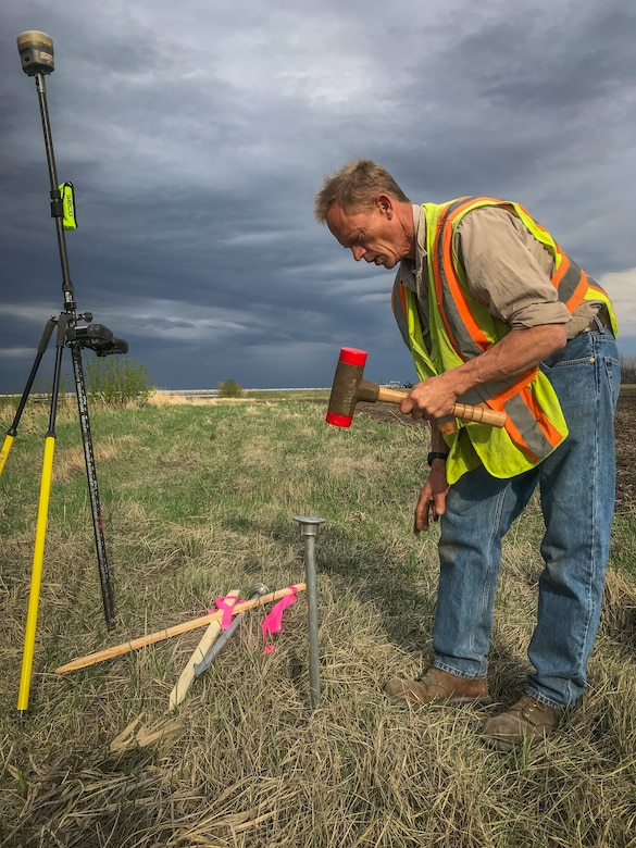 man pounds survey equipment into ground