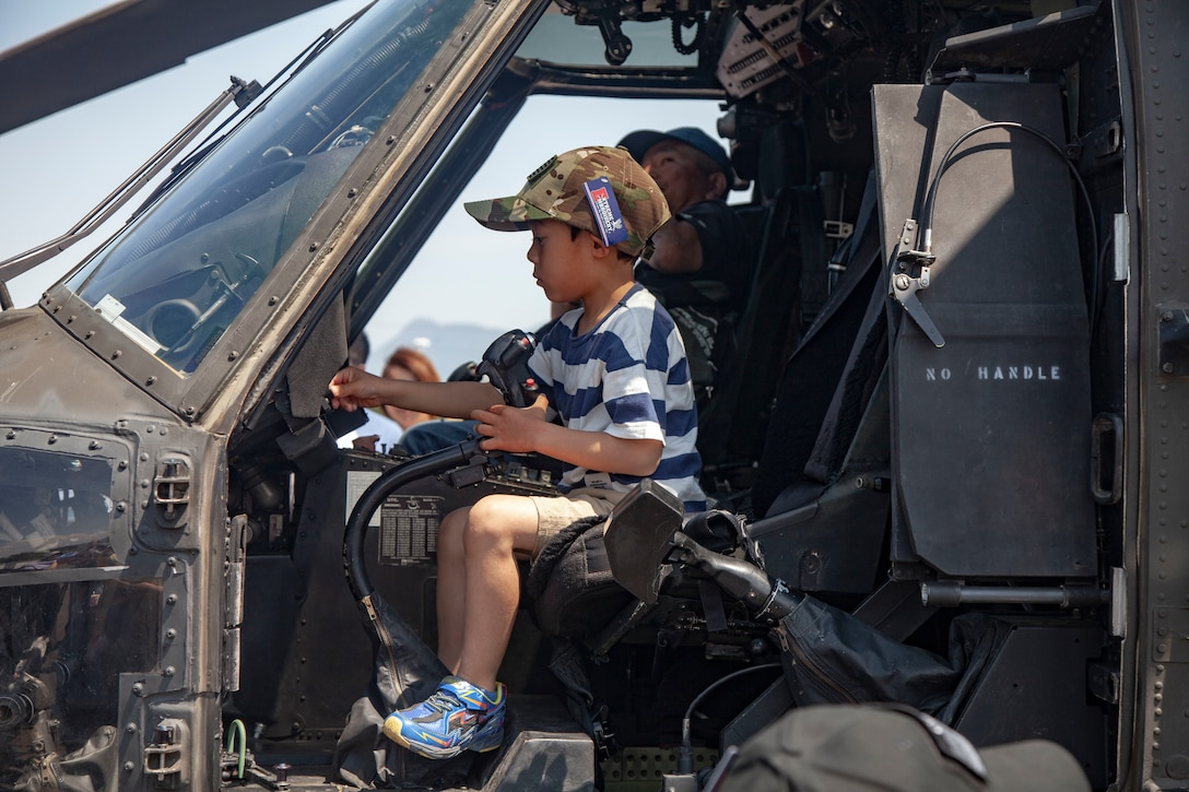 A local child explores the aircraft static display for the Friendship Festival May 11, 2019, on Combined Arms Training Center Camp Fuji, Shizuoka, Japan. The local community, Japanese Ground Self-Defense Force, and U.S. service members experience a day dedicated to Japanese and Marine Corps tradition and culture events.