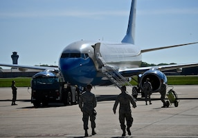 Airmen of the 932nd Maintenance Group move towing equipment toward a C-40C aircraft, to get it ready for another trip May 5, 2019, at Scott Air Force Base, Ill. All successful 932nd Airlift Wing C-40C mission launches start days earlier with mission planning, maintenance, and aircraft preparation. Another area behind the scenes that's important is keeping the ramps and parking spots clean and ready to launch missions. Time spent walking and getting eyes on the ramps protects tires and engines of all incoming and outgoing aircraft. This is done by manually collecting debris such as trash, blowing leaves, and small rocks or twigs, some dropped by birds flying over.  The 932nd Airlift Wing reservists maintain four of the unique C-40C planes.  (U.S. Air Force photo by Lt. Col. Stan Paregien)