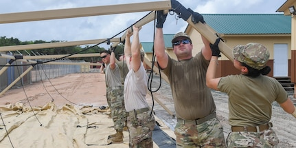 U.S. Air Force Airmen assigned to the 52nd Combat Communications Squadron at Robins Air Force Base, Georgia, construct the communications tent during New Horizons exercise at Camp Seweyo, Guyana, May 11, 2019.